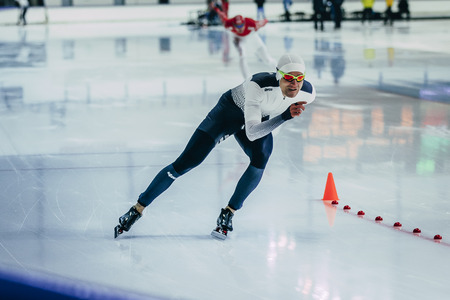 rival rivals rivalry season: Chelyabinsk; Russia - December 3; 2015: man athlete speedskater during race sprint distance along path of ice Palace during Cup of Russia on speed skating
