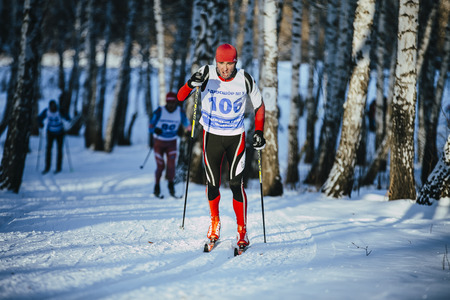 rivalry: Chelyabinsk, Russia -  December 19, 2015: rivalry young athlete skiers race in winter forest classic style during Championship of Chelyabinsk in cross-country skiing