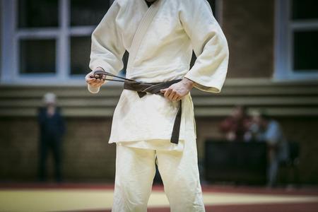 judo: primer plano cinturón marrón joven judoka para atar el kimono de judo durante las competiciones Foto de archivo