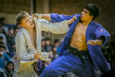 judo: Chelyabinsk, Russia -  December 20, 2015: young judoists during fight hold each other for kimono during All-Russian competition on judo of memory Grigory Verichev