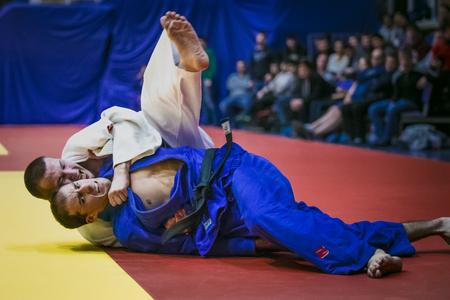 judo: Chelyabinsk, Rusia - 20 de diciembre de 2015: luchar contra el tatami dos luchadores de los atletas en las finales durante la competición de toda Rusia en el judo de la memoria Grigory Verichev