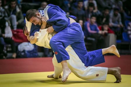 judo: Chelyabinsk, Rusia - 20 de diciembre de 2015: luchar contra el tatami dos atletas judocas varones en la final. en ventiladores de fondo durante la competición de toda Rusia en el judo de la memoria Grigory Verichev Editorial