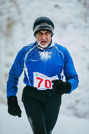 rival rivals rivalry season: Chelyabinsk, Russia -  January 5, 2016: elderly athlete man running on snowy Park alley. face in frost during Chelyabinsk winter marathon Editorial
