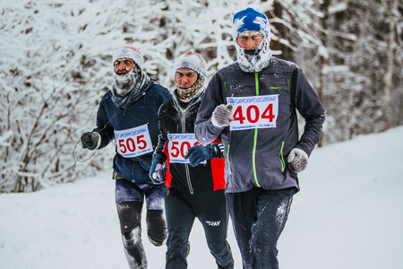 age 5: Chelyabinsk, Russia -  January 5, 2016: group men middle age runners running in cold weather in forest during Chelyabinsk winter marathon Editorial