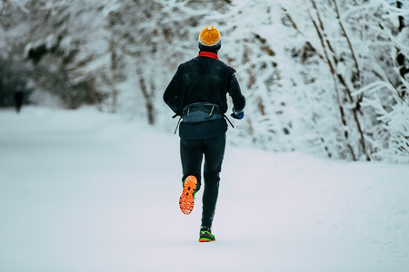 rival rivals rivalry season: male athlete running in winter woods. snow and cold weather