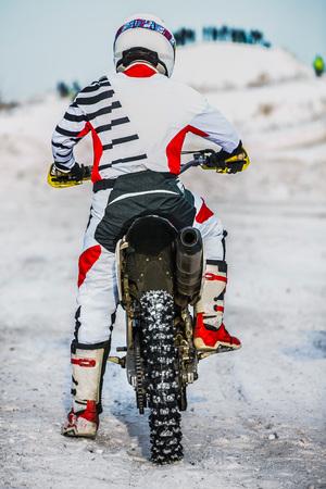 motociclista: motociclista corredor de cerca durante una carrera de invierno. vista trasera
