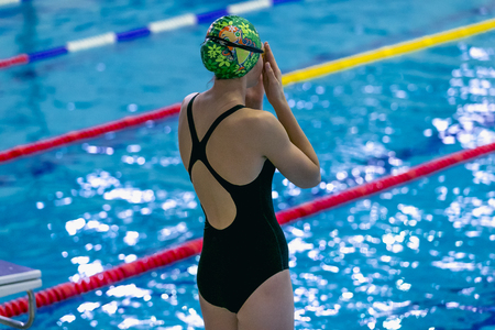 rival rivals rivalry season: girl is preparing for swimming in stands on side of pool Stock Photo