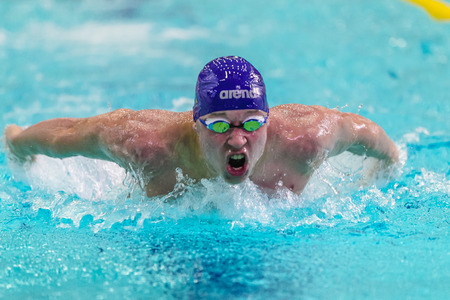 rival rivals rivalry season: Chelyabinsk, Russia - February 2, 2016: closeup of male athlete swimming butterfly stroke in pool during Championship of Ural Federal District in swimming
