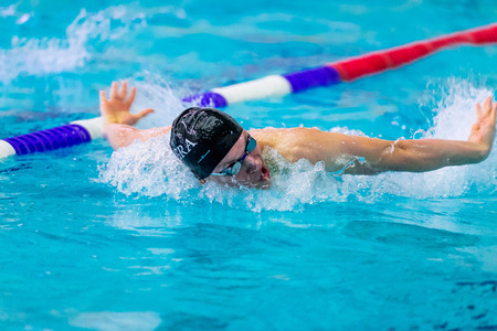 rival rivals rivalry season: Chelyabinsk, Russia - February 2, 2016: male athlete swimming butterfly stroke in pool during Championship of Ural Federal District in swimming
