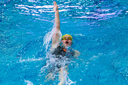 backstroke: Chelyabinsk, Russia - February 2, 2016: young female athlete swimming backstroke in sprint distance in pool during Championship of Ural Federal District in swimming