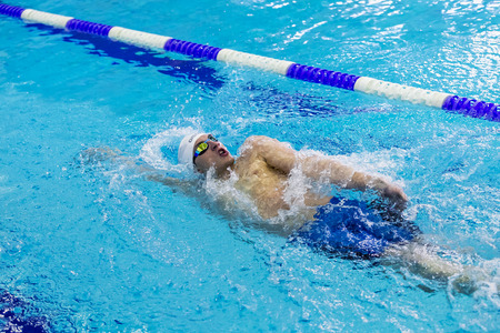 backstroke: Chelyabinsk, Russia - February 2, 2016: young male athlete swimming backstroke in sprint distance in pool during Championship of Ural Federal District in swimming