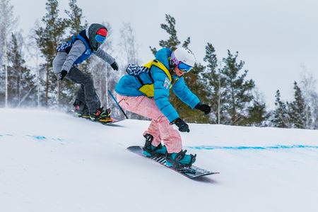 rivals rival rivalry season: Miass, Russia - February 3, 2016: two young girl athlete of snoubordisty downhill competition during Championship of Russia in snowboarding discipline: snowboard cross