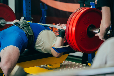 powerlifting: male athlete bench press at powerlifting competition