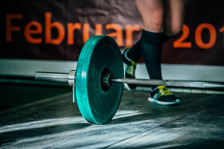 barbel: barbel deadlift on a wooden floor. athlete of powerlifter is preparing to attempt