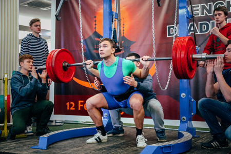 powerlifting: Chelyabinsk, Russia - February 12, 2016: young athlete of powerlifter squats barbell during West Asian championship 2016 WPC-AWPC powerlifting Editorial