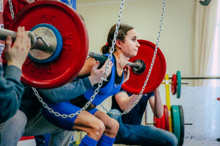 powerlifting: Chelyabinsk, Russia - February 12, 2016: female athlete of powerlifter squats barbell during West Asian championship 2016 WPC-AWPC powerlifting