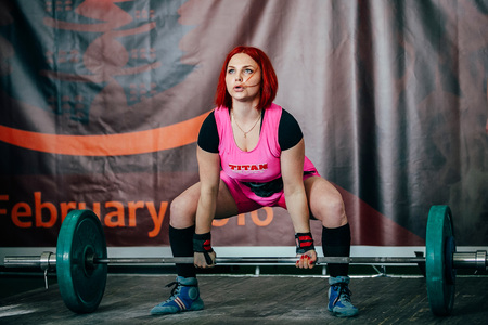 powerlifting: Chelyabinsk, Russia - February 12, 2016: young female athlete performs deadlift barbell during West Asian championship 2016 WPC-AWPC powerlifting Editorial