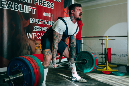 powerlifting: Chelyabinsk, Russia - February 12, 2016: man athlete of powerlifter attempt deadlift heavy barbell during West Asian championship 2016 WPC-AWPC powerlifting