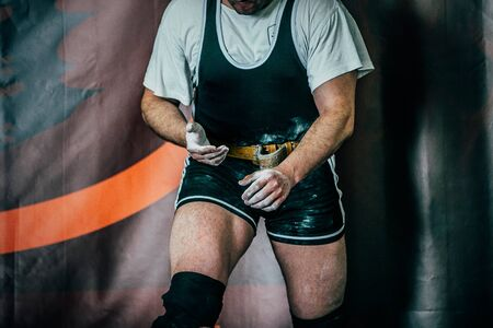 magnesia: powerlifter preparing for deadlift of barbell. hands powerlifter in magnesia Stock Photo