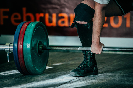 powerlifting: closeup of a male athlete deadlift in competition in powerlifting
