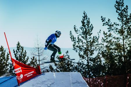 springboard: Miass, Rusia - 20 de febrero de, 2016: snowboarder joven atleta de salto de trampolín durante la Copa del Mundo de Snowboard - Snowboard Cross Editorial