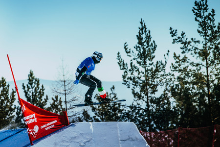 trampoln: Miass, Russia - February 20, 2016: young athlete snowboarder jumping springboard during Snowboard World Cup - Snowboard Cross