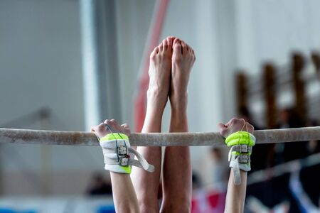 magnesia: hands and feet young girl gymnast exercises on bar Stock Photo