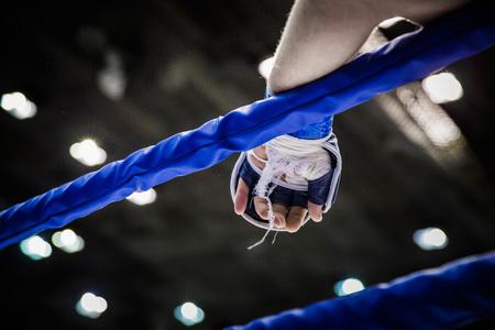 artes marciales mixtas: mano del luchador en cuerdas de anillo durante la competencia en las artes marciales mixtas