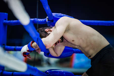 depletion: loser of fight boxer on ropes of corner ring after fight Editorial