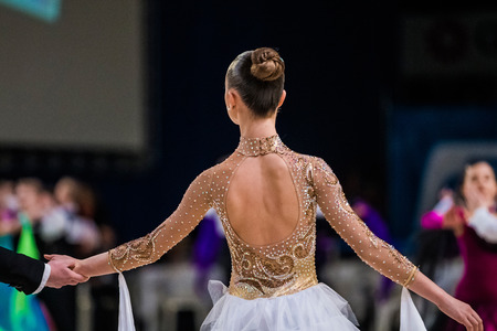 graceful young girl dancer ballroom dancing. view from back