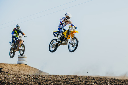 may fly: Miasskoe, Russia - May 02, 2016: two riders on motorcycles jump from mountain and fly during Cup of Urals motocross