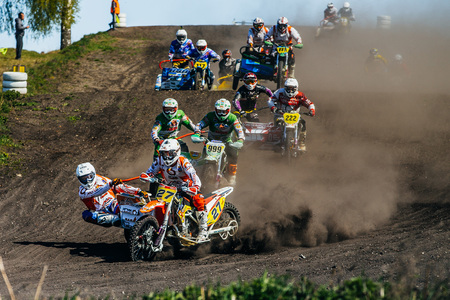 sidecar motocross racing: Miasskoe, Russia - May 02, 2016: group of motorcyclists with sidecars riding along a dusty track during Cup of Urals motocross
