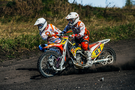 sidecar motocross racing: Miasskoe, Russia - May 02, 2016: closeup of a motorcycle with sidecars riding along a dusty track during Cup of Urals motocross