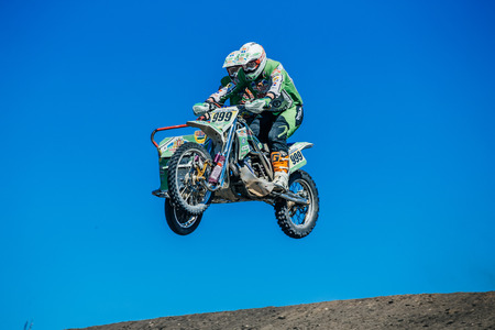 sidecar motocross racing: Miasskoe, Russia - May 02, 2016: motorcyclist with a sidecar jump from a mountain on background of blue sky during Cup of Urals motocross
