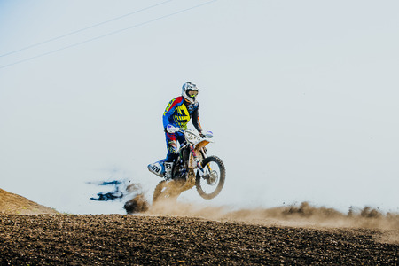 rear wheel: Miasskoe, Russia - May 02, 2016: racer on a motorcycle rides on rear wheel on a dusty track during Cup of Urals motocross Editorial