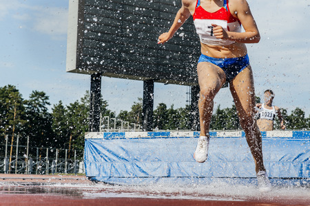 steeplechase: woman athlete runs steeplechase at stadium during competition. a spray of water Stock Photo