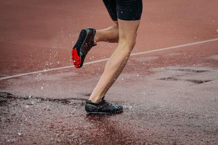 steeplechase: athlete foot men running steeplechase. a spray of water