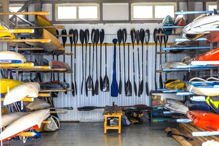 stockroom: warehouse for storage of boats, canoes and kayaks, paddle Stock Photo