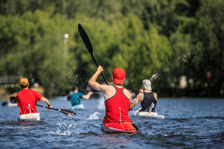 group of athletes canoeists boating on  lake in a kayak. water spray from oars