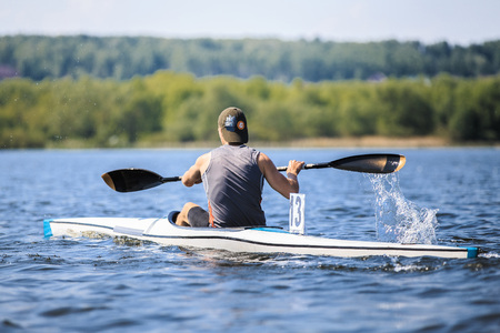 Athlete Rower On Rowing Kayak Lake During Competition Splashes Of Water Under Paddle Photo
