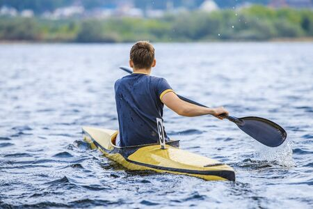 boating: young man in a canoe rowing oars. boating in  lake