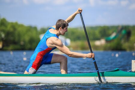 canoeist: Chelyabinsk, Russia - May 28, 2016: closeup of athlete canoeist rowing with an oar in a canoe during Ural championship in rowing