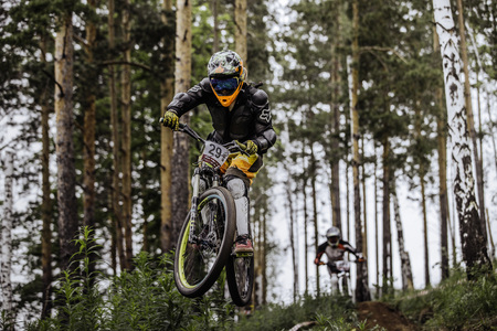 may fly: Miass, Russia - May 29, 2016: jump and fly racer on bike in woods during Cup Ryder downhill
