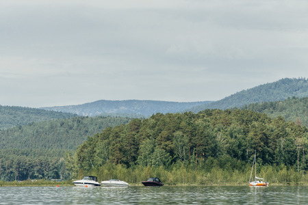 motor boats: motor boats and yacht stand at shore of lake on background of mountains and forest
