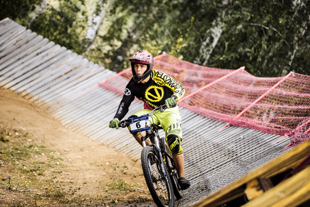 berm: Magnitogorsk, Russia - July 23, 2016: athlete man extreme cyclist riding Insloped Turn during National championship downhill Editorial
