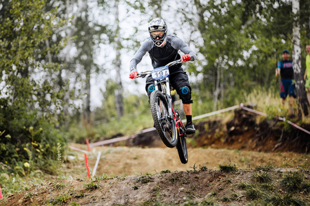 national championship: Magnitogorsk, Russia - July 23, 2016: jump over hill male extreme athlete bike during National championship downhill