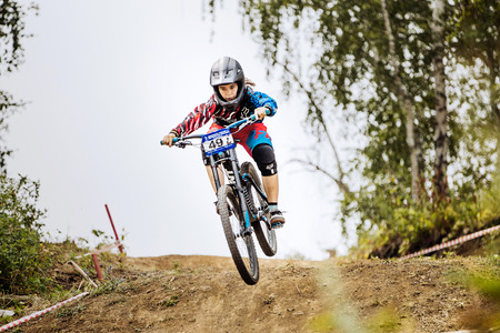 national championship: Magnitogorsk, Russia - July 23, 2016: jump over mountain girls extreme athlete bike during National championship downhill