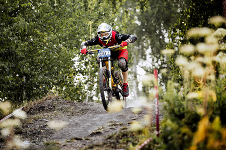 magnitogorsk: Magnitogorsk, Russia - July 23, 2016: male extreme racer on bike rides over rocks in forest during National championship downhill