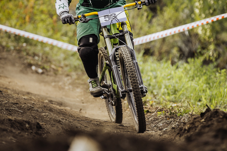 downhill: racer on bike rides forest trail during race downhill