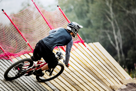 berm: athlete man extreme cyclist riding Insloped Turn during competitions in downhill